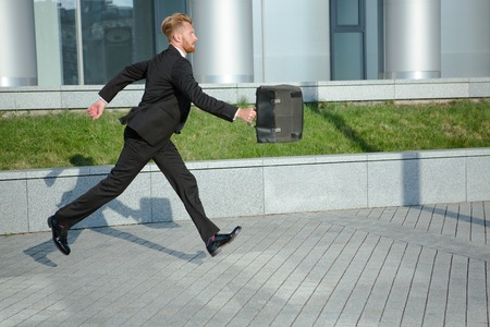 running late: Businessman with brief case in hurry. Red-haired man in black business suit running to the office not to be late for conference. Stock Photo
