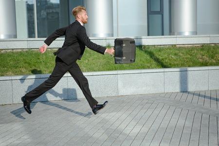 llegar tarde: Hombre de negocios con malet�n en la prisa. Hombre pelirrojo en traje de negocios negro corriendo a la oficina para no llegar tarde a la conferencia.