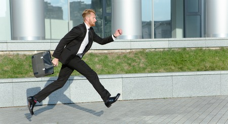 hurrying: Handsome modern hipster businessman with bag hurrying to work. Red-haired man in black business suit does not want to miss meeting.