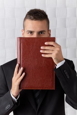 traje sastre: Sonriente hombre de negocios con los ojos marrones se esconden detr�s del registro de color rojo oscuro. El hombre con el pelo corto en traje de negocios es verdadero profesional en su �mbito.