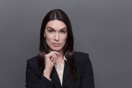 industrious: Portrait of business lady in black suit keeping her chin. Woman with long black hair looking so seriou and industrious isolated on grey.