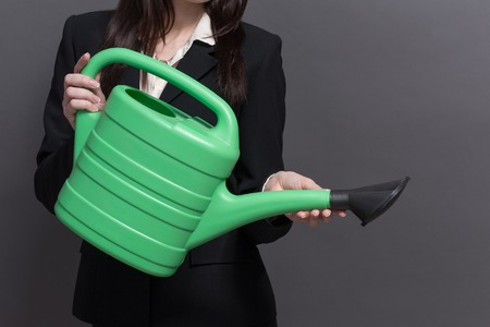 business suit: Close-up portrait of green watering pot isolared on grey. Woman in black business suit demonstarting how to earn much money.