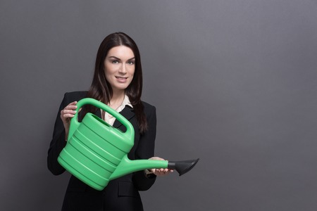 watering pot: Young attractive businesswoman with green watering pot. Woman in black business suit ready to increase the profit of her company.