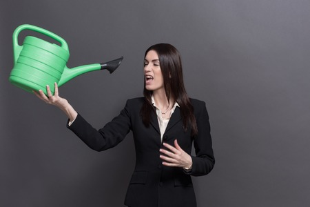 watering pot: Business lady posing with green watering pot. Young long-haired woman bevelling and looking at watering pot on grey background. Stock Photo