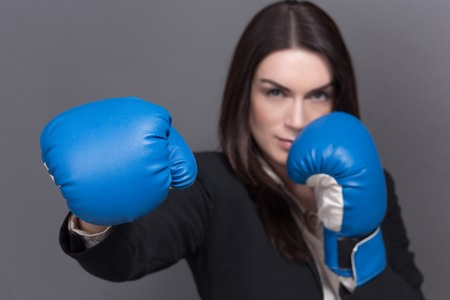 Young businesswoman in boxing concept. Pretty woman with long black hair posing for photographer isolated on grey.