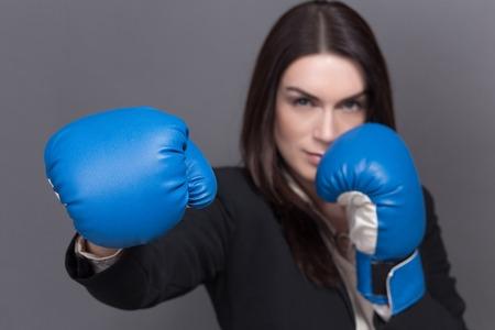 guantes de box: Joven empresaria en el concepto del boxeo. Mujer bonita con el pelo largo y negro posando para el fotógrafo aislado en gris.