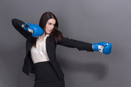 office politics: Portrait of serious woman in gloves. Young businesswoman in blue boxing gloves as a metaphor for office politics on grey background. Stock Photo