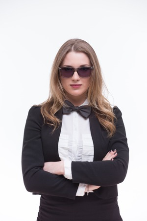 businesswoman suit: Business lady posing in sunglasses. Woman in black business suit seriously standing with her arms crossed on white background. Stock Photo