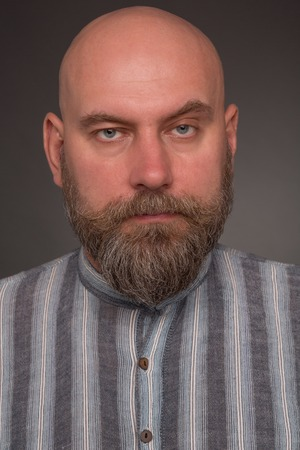 detained: Portrait of bearded man in prison garb. Bold serious man in lined shirt posing on dark grey. Stock Photo