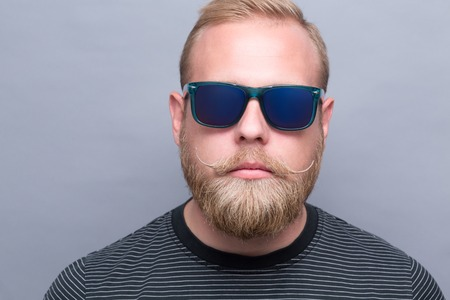 ambitious: Close-up portrait of serious bearded man on grey. Short-haired ambitious man promoting up-to-date navy blue sunglasses.
