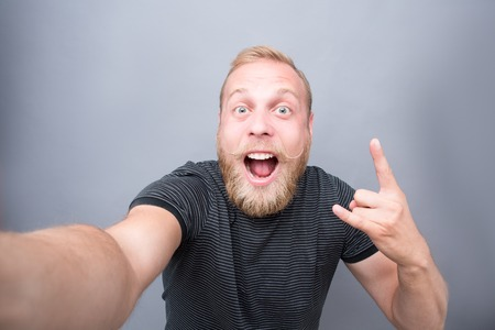 Bearded man showing yo sign on grey background. Man with blond hair making selfies and happy smiling for the camera. 免版税图像