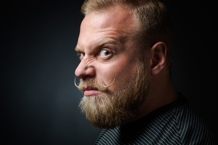 narrowing: Profile of demanding blond bearded man on black background. Serious man looking so strange and narrowing his eyes because of annoyance. Stock Photo