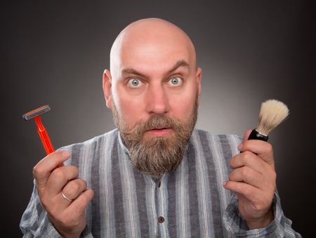 jailbird: Astonished jailbird posing with razor and brush in his hands. Bold bearded man is very surprised isolated on dark grey. Stock Photo