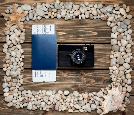 pasaporte: Pasaportes, billetes y la cámara están en el marco de las conchas marinas y piedras. Hermoso marco hecho de la colección de objetos náuticos y de playa.