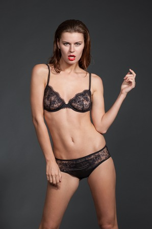 bikini slender: Young sexy slim and slender woman in black bikini in photostudio. Woman with long red hair is professional top model.