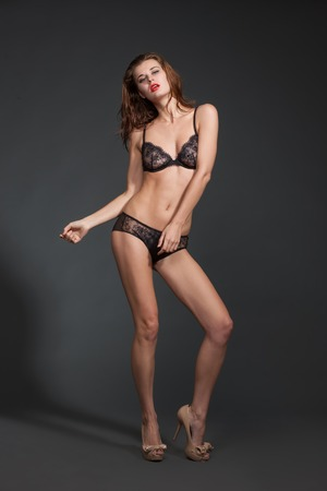 owing: Full length portrait of stunning young woman posing in bikini over grey background. Model with red lips owing sexy body.