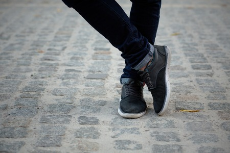 adult foot: Close-up picture of man who crossed his legs. Man in black jeans and sneakers enjoying daytime in the city. Stock Photo