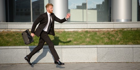 Handsome businessman running with brief case in hand. Successful man with red hair in business suit dreaming about succeeding.