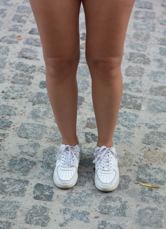 jogging shoes: Close-up picture of attractive womans legs. Beautiful slender female legs in white jogging shoes.