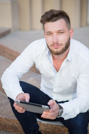 demanding: Young handsome businessman posing with tablet pc outdoors. Short-haired bearded man in white shirt looking so serious and demanding. Stock Photo