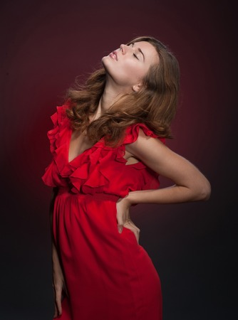 Beautiful elegant fashion model in red dress. Top model with red hair closed her eyes isolated on dark red background.