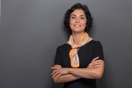neckcloth: Close-up portrait od air stewardess isolated on grey. Smiling adult lady in black dress and yellow neckcloth posing with her arms crossed.