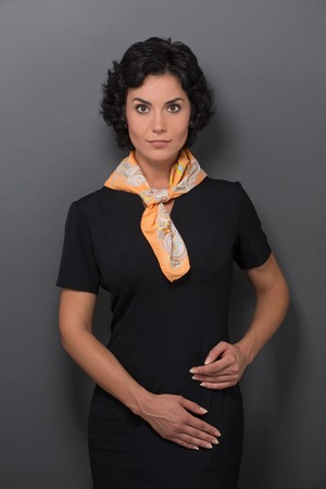 neckcloth: Beautiful young flight attendant in black clothing isolated on grey background. Happy woman with yellow neckcloth looking so serious. Stock Photo