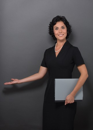 black dress: Business concept. Smiling businesslady in black dress demonstrating something with her hand on grey and keeping files.