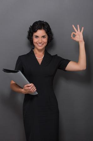 Empresaria hermosa que muestra bien firmar y sonriendo para la cámara. Señora con pelo celebración documentos en blanco en su mano sobre gris. Foto de archivo