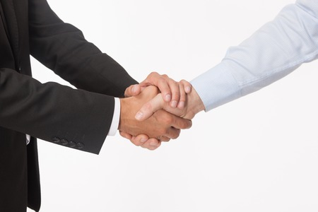 Welcoming business partners handshake. Two successful businessmen standing and looking at each other shaking hands. 免版税图像