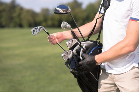 Golf and golfer concept. Man in white T-shirt removing a golf club from his golf bag to start playing professional golf over green course.