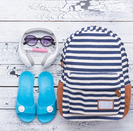 blank space: Close-up lifestyle photo of hipster summer objects isolated on white wooden background: bag, earphones, flip flops, sunglasses and lip gloss. Stock Photo