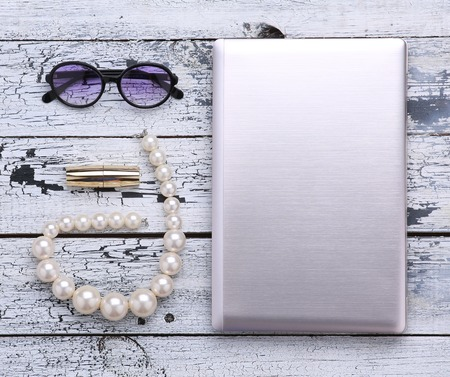 evenings: Represented objects are nice idea to work during your vacation. Laptop is for freelance. Sunglasses, lipstick and beads are for spending evenings. Stock Photo