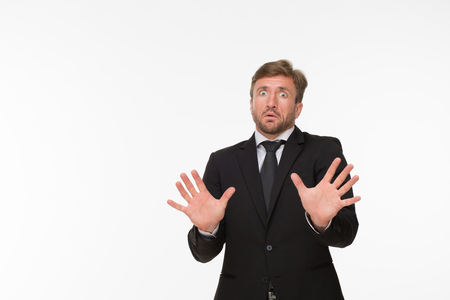 Picture of frightened businessman isolated on white background. Man in business suit showing fear with his hands.