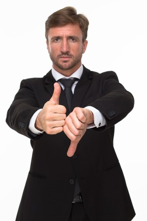 dissatisfaction: Picture of handsome bearded businessman showing thumbs up and down. Serious man expressing his negativity, dissatisfaction and positivity.