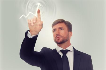 gobierno corporativo: Dibujo de la mano del hombre de negocios cada vez mayor gr�fico en la pantalla de los medios. Hombre serio que tiene el deseo de ver la prosperidad de su empresa.