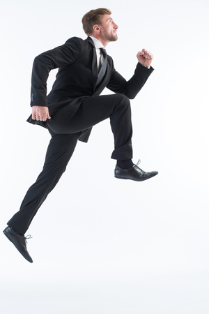 Picture of businessman running up imaginative stairs isolated on white. Serious man in black business suit is in a hurry.