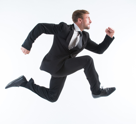 Business concept. Running young businessman excited, surprised and happy amazed isolated on white background. 免版税图像