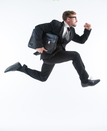 Businessman running with a briefcase isolated on white background. Successful man in glasses is in a hurry.