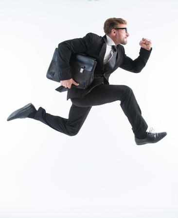 Zakenman loopt met een aktetas op een witte achtergrond. Succesvolle man met een bril is in een haast. Stockfoto