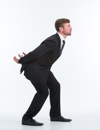 carry on: Business concept. Full length studio shot of a well dressed businessman pretending to carry a heavy invisible load on his back.