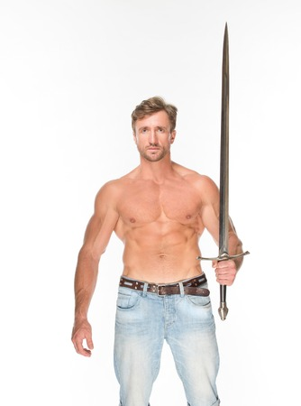 barechested: Bare-chested man holding katana sword in his left hand in front of him. Serious handsome man posing in photo studio isolated on white background. Stock Photo