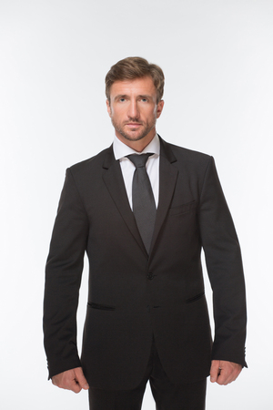 industrious: Portrait of handsome businessman in black business suit posing. Man with short hair looking so serious and industrious. Stock Photo