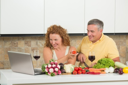 Happy mature couple using laptop computer in home. People are in search of recipes for preparing something from fresh vegetables in the kitchen.