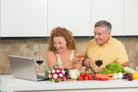 cocina saludable: Feliz pareja madura utilizando equipo port�til en casa. La gente est� en busca de recetas para preparar algo de verduras frescas en la cocina.