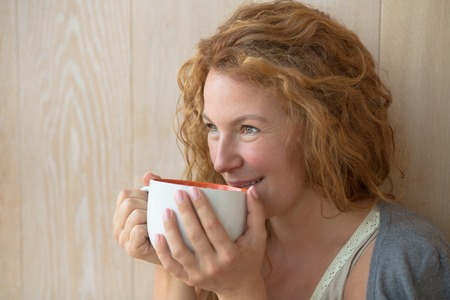 working week: Smiling middle-aged woman drinking a cup of delicious tea near wall. Beautiful lady relaxing at weekends after hard working week.