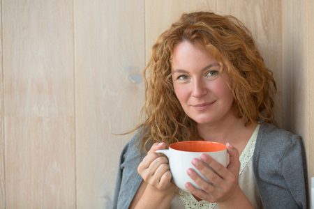 Portrait of beautiful middle-aged woman posing with a cup of tea or coffee. Happy lady with red hair looking at the camera. Stock Photo
