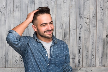 camisas: Hombre inconformista guapo peinarse el cabello grueso. Hombre elegante y con estilo en jeans camisa sonriendo y mirando a otro lado aislado en madera.
