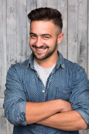 Happy smiling hipster man over wooden background. Handsome bearded man posing with woth arms crossed. 免版税图像