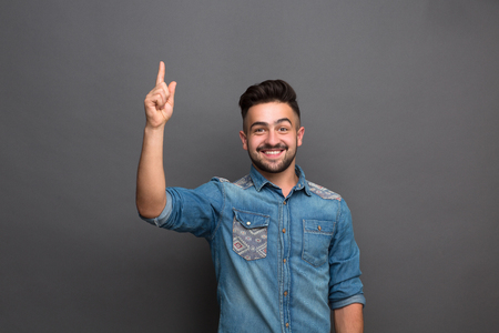 Handsome hipster man smiling and showing point finger. Bearded man in jeans shirt happy smiling in studio isolated on grey.